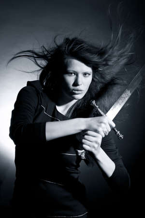 The beautiful young woman holds a sword in a hand Stock Photo - 8194061
