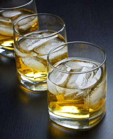 Whisky with ice in glasses on a black background photo