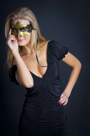 The young woman with a mask on the person. Dark background Stock Photo - 8713593