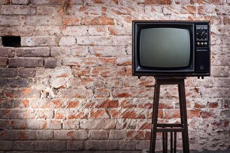 television antigua: El viejo televisor contra un antiguo muro de ladrillo Foto de archivo