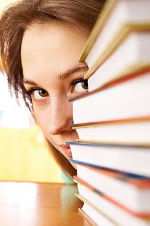 The young woman looks out from for piles of books. A close up Stock Photo - 9219114