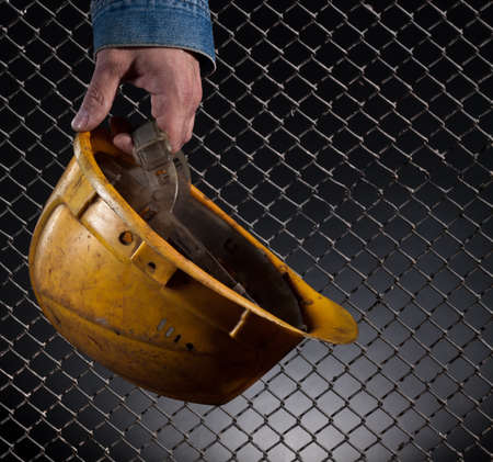 precaution: The hand of the worker holds a old helmet. A close up