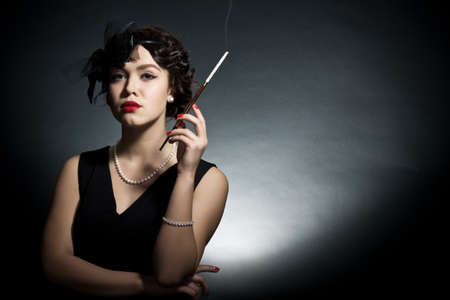 women smoking: Portrait of the young woman in style of a retro against a dark background