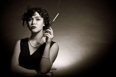 chica fumando: Retrato de la joven en estilo retro contra un fondo oscuro