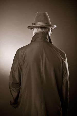 レインコートおよび帽子の男。背面ビュー