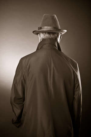 mystery man: The man in a raincoat and a hat. The rear view  Stock Photo