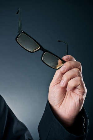 eyesight: glasses in a hand of the man against a dark background  Stock Photo