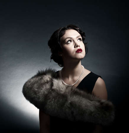Portrait of the young woman in style of a retro against a dark background photo