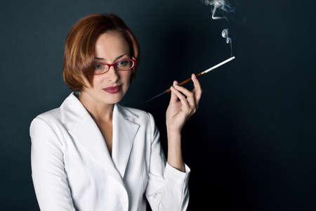 The young woman smokes a cigaret photo