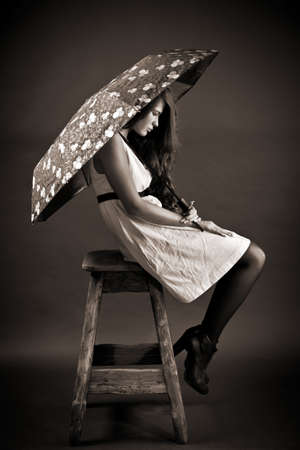 strangeness: The young woman with an umbrella sits on a high stool Stock Photo