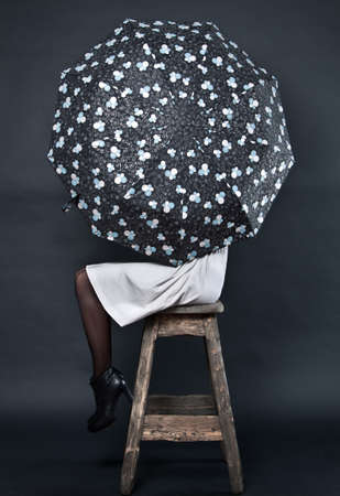The young woman with an umbrella sits on a high stool Stock Photo - 10767517