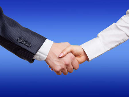 clasped hand: Handshake by close up on a blue background Stock Photo