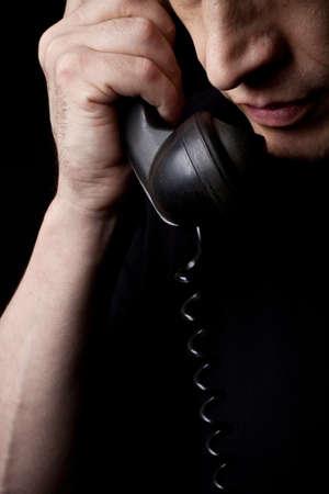 男は携帯電話で話します。A のクローズ アップ。黒の背景