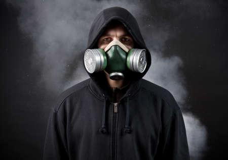 gasmasker: De jonge man in een capuchon en in een respirator