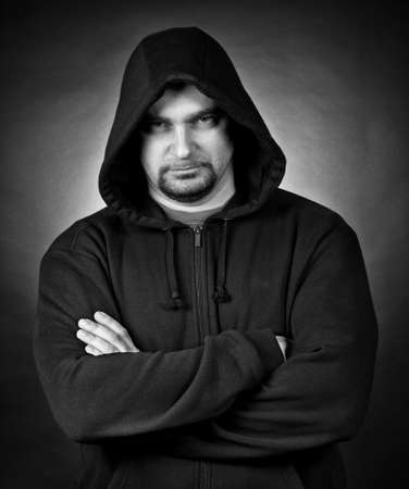 mystery man: Portrait of the man in a hood against a dark background Stock Photo