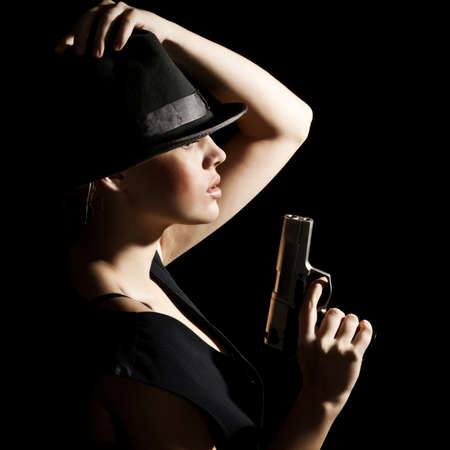 The young woman in a hat and with a pistol. A black background photo