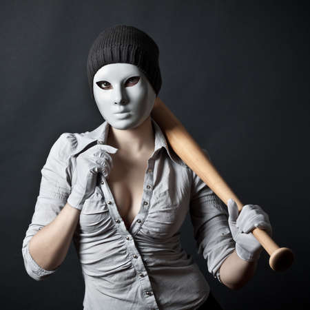 scary girl: The teenager in a mask and with a bat