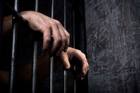 preso: Las manos del prisionero en una retícula de acero de cerca