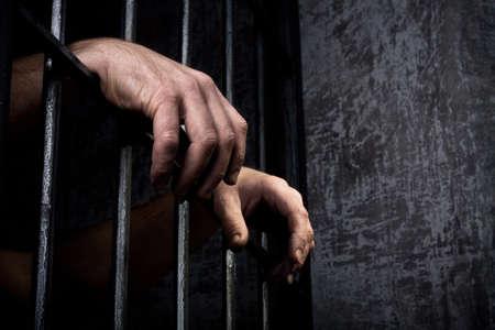 cellule prison: Mains de la prisonni�re sur un treillis d'acier de pr�s