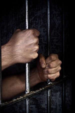 gefangener: Hände des Gefangenen auf einem Stahlgitter hautnah Lizenzfreie Bilder