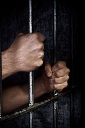 preso: Las manos del prisionero en un enrejado de acero de cerca