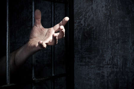 trapped: Hand of the prisoner on a steel lattice close up Stock Photo