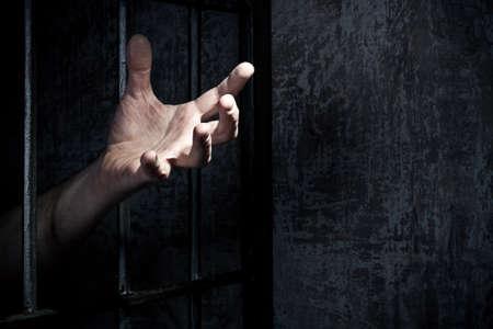 cellule de prison: Main du prisonnier sur un treillis d'acier de près Banque d'images