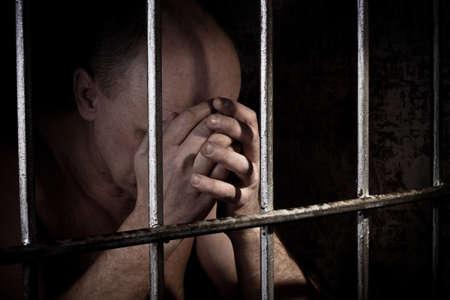 cellule de prison: Le prisonnier inquiète au sujet d'un comportement criminel étant derrière un treillis