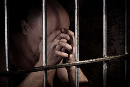 prisoner man: The prisoner worries about a criminal conduct being behind a lattice Stock Photo