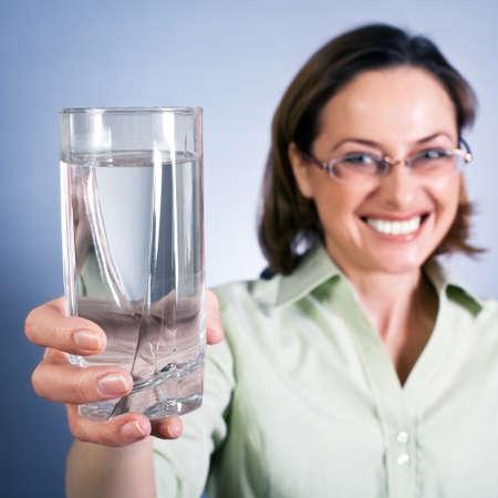 女性は手で純粋なばね水のガラスを保持します。