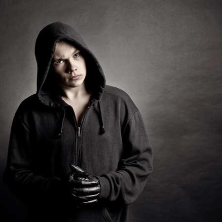 暗い背景に対してフードに若い男の肖像