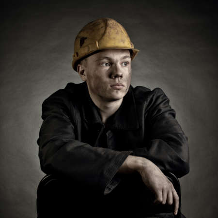 COAL MINER: Portrait of the young worker against a dark backgroun Stock Photo