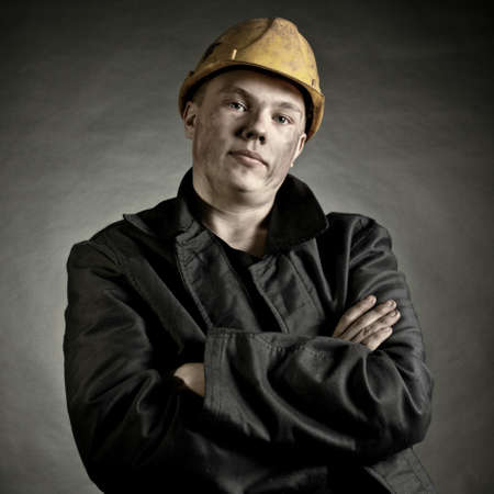 grime: Portrait of the young worker against a dark backgroun Stock Photo