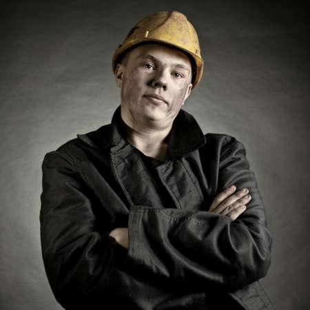 trabajando duro: Retrato del joven trabajador en contra de un backgroun oscura