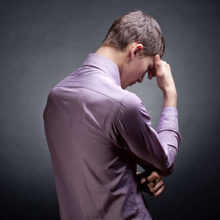 man praying: The young man reflected. Dark background