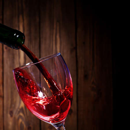 wine background: red wine flows in a glass