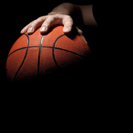 basketball ball: fragment of a basketball ball in a hand of the basketball player Stock Photo