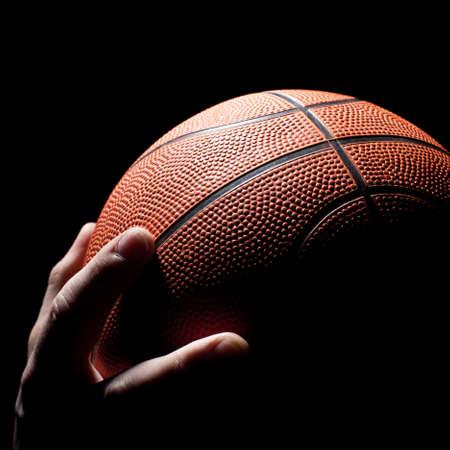 balon baloncesto: fragmento de de una pelota de de baloncesto en una mano de el jugador de baloncesto Foto de archivo