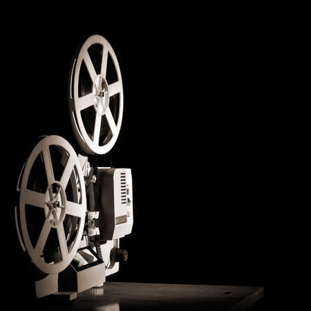 movie film reel: Old film projector on a black backgroun