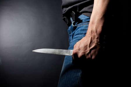 the knife: El hombre con un cuchillo en una mano. Primer plano Foto de archivo