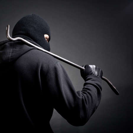 balaclava: A burglar with a crowbar on the shoulder  View from the back