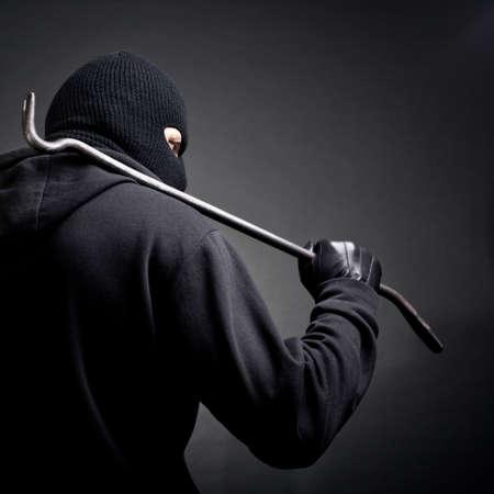 Een inbreker met een koevoet op de schouder Uitzicht vanaf de achterkant Stockfoto