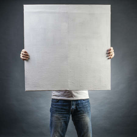 surrealism: male holds a square canvas primed