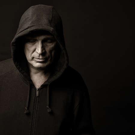 暗い背景に対してフードに男の肖像