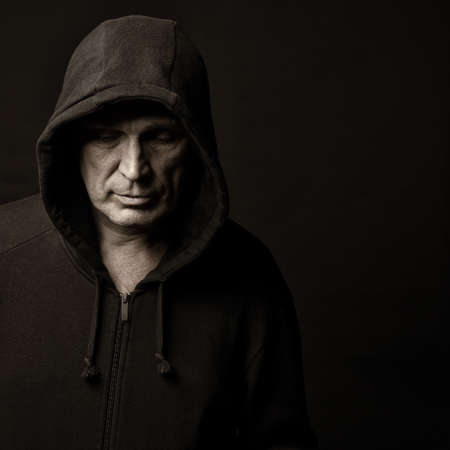 hoodlum: Portrait of the man in a hood against a dark background Stock Photo