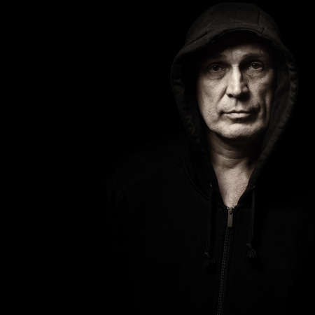 hooded: Portrait of the man in a hood against a dark background Stock Photo