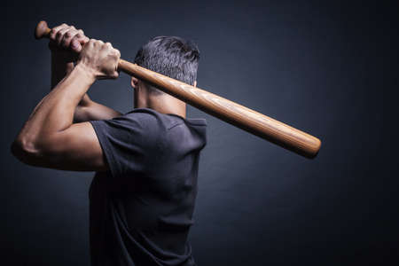 baseball bat: Man swung the bat. View from the back