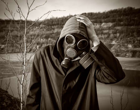 A man in a gas mask grabbed his head by hand Stock Photo - 15831812