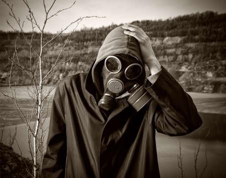 gasmasker: Een man in een gasmasker pakte zijn hoofd met de hand Stockfoto
