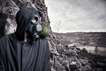 Portrait of a man in a gas mask and hood against the fading landscape photo
